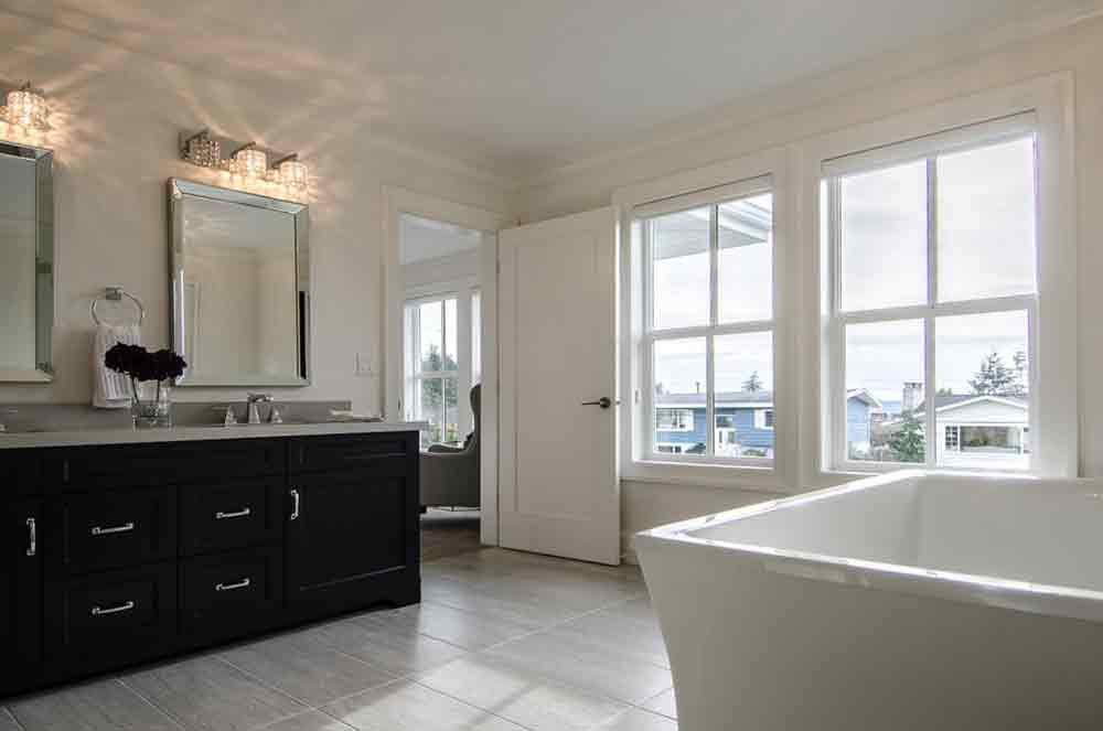 white bathroom with dark brown cabinet and tub